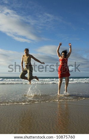 Two woman jumping in a sunny beach - stock photo