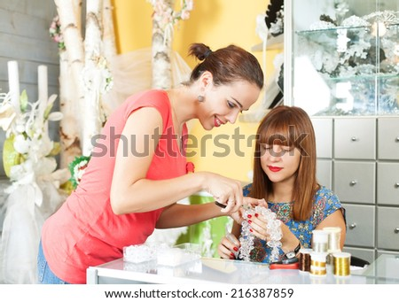 Two woman making jewelry in a accessory shop - stock photo