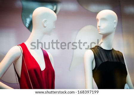 Two woman mannequins in red and black dresses in shopping window in store (selective DOF)