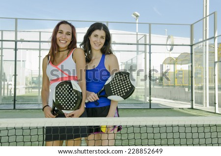 Two woman posing on paddle tennis court - stock photo