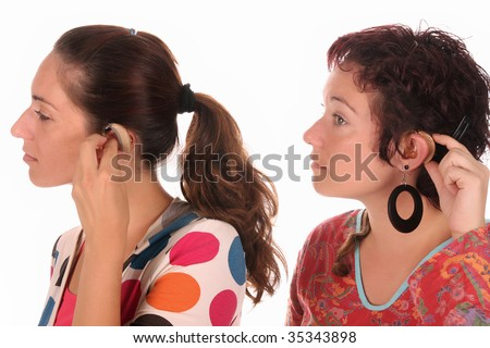Two woman putting hearing aid into ear - stock photo