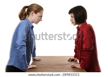 two woman stand over a table not looking very happy  - stock photo