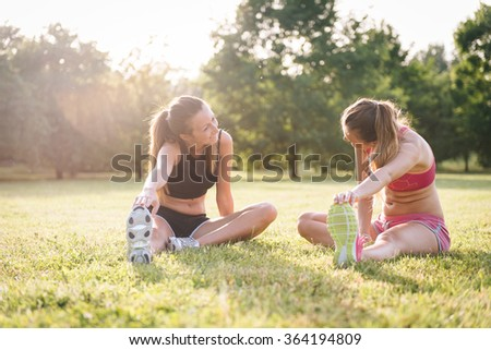 Two woman stretching at the park - stock photo