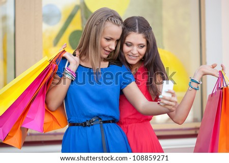 two woman taking pictures of themselves with phone camera - stock photo