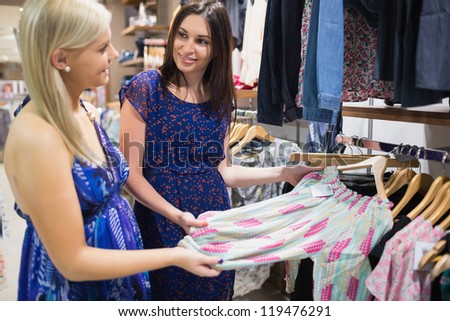 Two woman talking beside clothes rail in shopping mall - stock photo