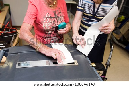 Two woman with their ballots are gonna put them in a ballot box - stock photo