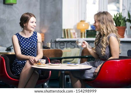 Two womans make dialogue and snile over joke - stock photo