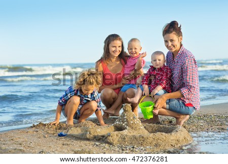 Two Womans with children playing on the beach