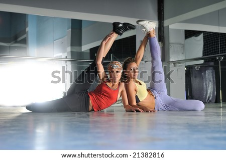 two womans work out and streaching legs in fitness club - stock photo