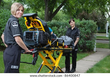 Two women ambulance workers with stretcher in rural area - stock photo