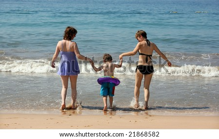 Two women and a baby walking into the ocean - stock photo