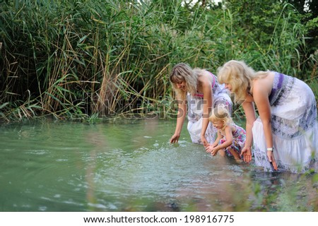 two women and a child in national costumes splashing in the river