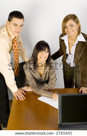 Two women and a man are at the desk. One of the women's sitting. They are all smiling to the camera.