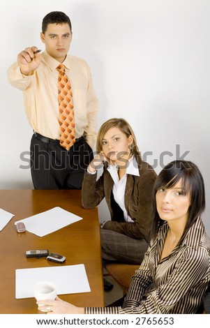 Two women and a man are at the table. Man's standing and pointing screen (camera).