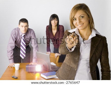 Two women and a man are standing at the conference's table. There's working multimedia projector on it and laptop. Woman on the front is pointing. - stock photo