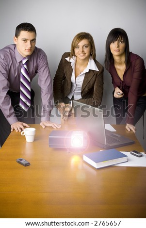 Two women and a man are standing at the conference's table. There's working multimedia projector on it and laptop.