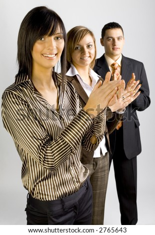 Two women and a man are standing, looking at the camera and clapping hands. Focus is on the first person. - stock photo