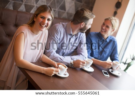 Two women and a man at cafe, talking, laughing and enjoying their time.