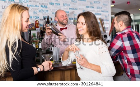 Two women and a man at the bar. Women are talking and a man is waiting for his drink while the bartender is mixing it in a shacker - stock photo