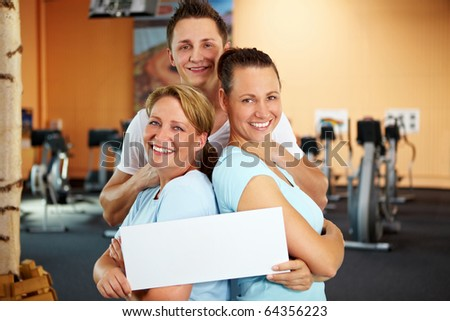 Two women and a man holding an empty sign in a gym - stock photo