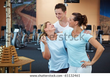 Two women and a man talking in gym - stock photo