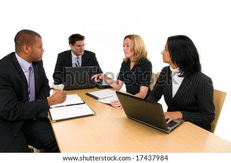 Two women and a two men sit at conference table at a business meeting