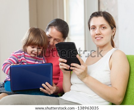 Two women and child using electronic devices on sofa  in home - stock photo