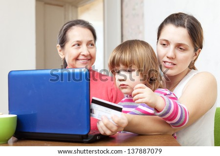 Two women and child with laptop, paying by credit card in internet store - stock photo