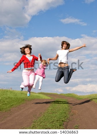 two women and one girl jump outdoor - stock photo
