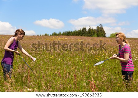 two women are playing badminton in a meadow - stock photo