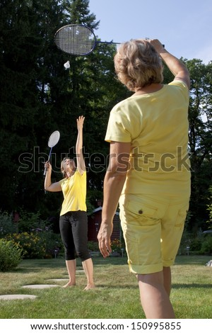 Two women are playing badminton in the garden - stock photo