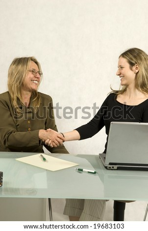 Two Women are sitting at a table in a business meeting.  They are shaking hands and smiling at each other.  Vertically framed shot. - stock photo