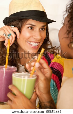 Two women are talking and enjoying smoothies together.  Vertical shot.