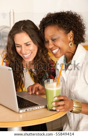 Two women are working on a laptop while enjoying smoothies.  Vertical shot. - stock photo