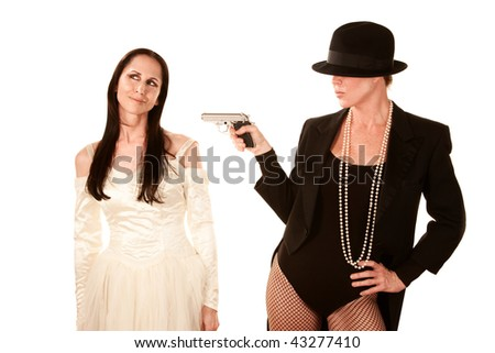 Two women as bride and groom with pistol aimed - stock photo