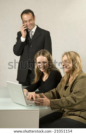 Two women at a desk and a man standing talking on his cell phone. All are smiling and looking at paperwork.