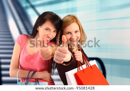Two women at the mall, thumbs up - stock photo