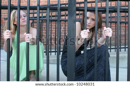 Two women behind fake bars