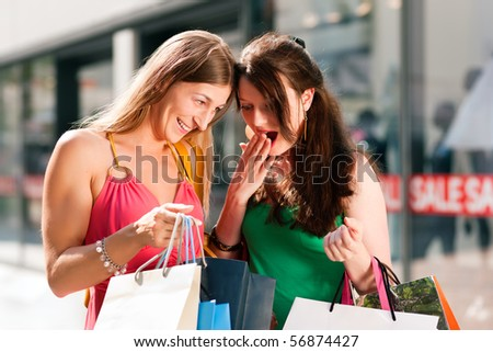 "Two women being friends shopping downtown with colorful shopping bags, in the background a store can be seen with the words ""sale"" in the window - stock photo"