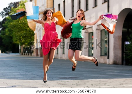 Two women being friends shopping downtown with colorful shopping bags, they are jumping for joy - stock photo