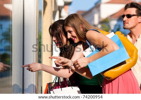 Two women being friends shopping downtown with colorful shopping bags, they are lolling into a glass store door and are amazed; in the background a man is standing - stock photo
