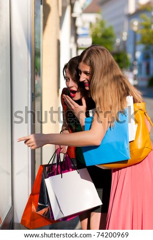Two women being friends shopping downtown with colorful shopping bags, they are lolling into a glass store door and are amazed - stock photo