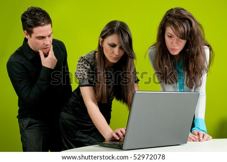 Two women being watched by their male colleague in the office