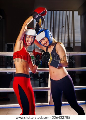 Two  women boxer wearing red  gloves and helmet to box in ring. Martial arts. - stock photo