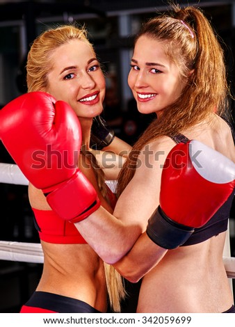 Two  women boxer wearing red  gloves posing and embracing  in ring. - stock photo