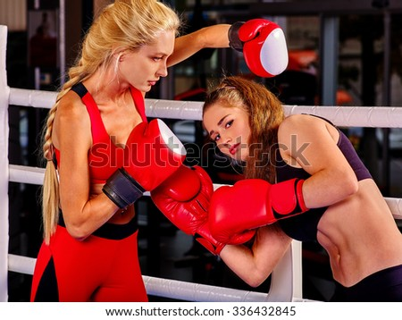 Two  women boxer wearing red  gloves to box in ring. Sport competition. - stock photo