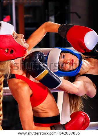 Two  women boxer wearing red  gloves to box in ring. Striking below the chin. - stock photo