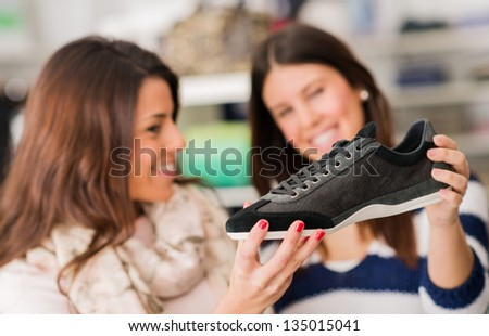 Two Women Buying Shoes, Indoors - stock photo