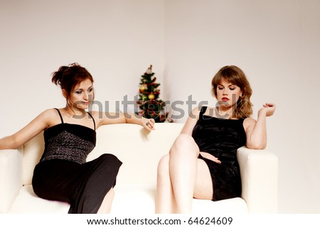 two women celebrate christmas in evening dress