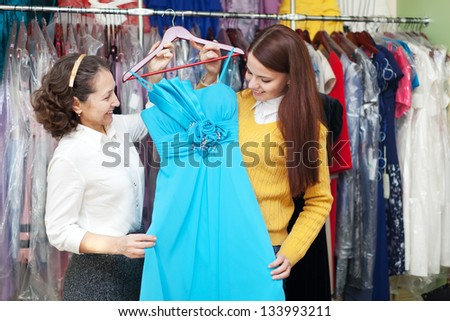 Two women chooses blue evening gown  shop of fashionable clothes - stock photo